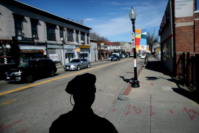 A Boston Police officer in silhouette on the street