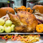 A photo of a turkey surrounded by apples, cranberries, pumpkins and gourds