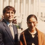 Photo of a printed photo of Jay Wexler (left) with Supreme Court Justice Ruth Bader Ginsburg in 1999, when he was one of her four clerks. Behind them is the facade of the Supreme Court. RBG wears a mustard colored shawl and Wexler wears a suit and tie.