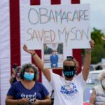 Adelys Ferro holds a sign in support of Obamacare at a Biden/Harris rally in Florida