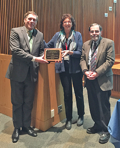 Anne Fidler, center, presents the Gail Douglas Award to Frank Giacalone, president of the Massachusetts Health Officers Association, who accepted on behalf of the Bureau of Infectious Disease. At right is Al Demaria, State Epidemiologist and previous winner of the award.
