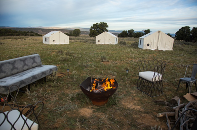 A fire pit surrounded by outdoor coaches and glamping tents