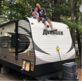 Members of Suzanne's family sitting on top of the family's trailer
