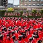 many grads sit on Nickerson Field with the Boston University sign visible during their commencement ceremony