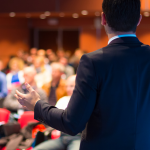 In focus we see the back of a man speaking at a conference to a crowd, which is blurred in the background