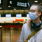 a girl in a mask stands alone in an empty airport