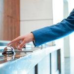 arm of person wearing a blue blazer reaches to press a bell on top of hotel lobby counter