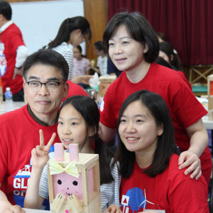 Young-chun Cho (clockwise from top left) his wife, Soojeong Kim, and their daughter Hyunjoo Cho work with an orphan from Dream Tree Village at a Global Days of Service event last year.