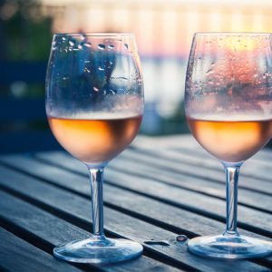 Two glasses of chilled rose wine on a picnic table