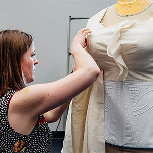 A theatre student working in the Boston University College of Fine Arts costume shop works tailoring a women's costume for the stage production of Angels in America.