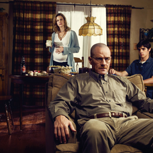 Breaking Bad character Walter White sits in a recliner with his family wife Skylar and son Walt Jr. in the background.