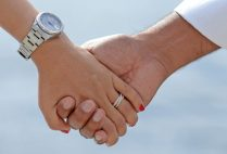 Detail photo of married couple holding hands