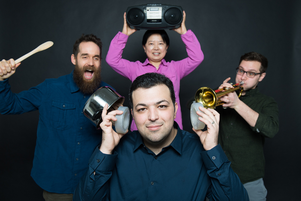 Boston University Ph. D. candidate Reza Ghaffarivardavagh poses with his research team. Reza holds the noise cancellation devices his team developed over his ears while his teammates make noise banging a pot, playing a trumpet, and a boombox in the background