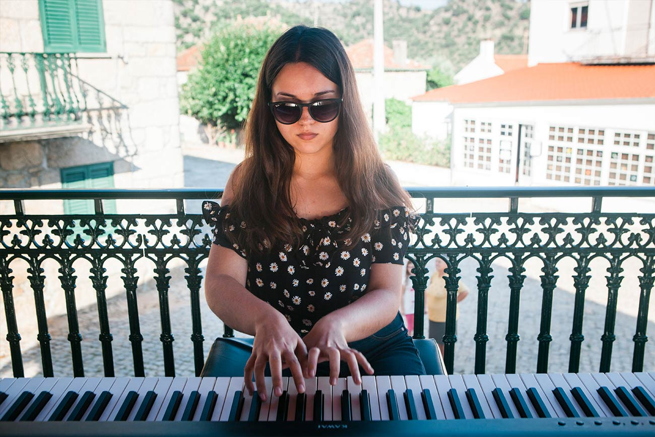 Full color slideshow photo of piano student Margarida Pacheco wearing sunglasses, performing on a digital piano for the villagers of Bendada in the coreto, a covered bandstand in the town square.