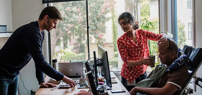 Craig Cloutier speaks to Rahul Desikan while Maya Vijayaraghavan helps Desikan sip a drink.