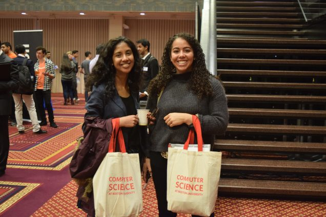 Two students pose with their CS Day swag bags.