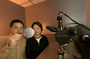 "Xin Zhang and former graduate student Shusen ""Forest"" Huang inspect arrays of tiny infrared sensors.  Huang graduated in May 2007 with a Ph.D. in manufacturing engineering."