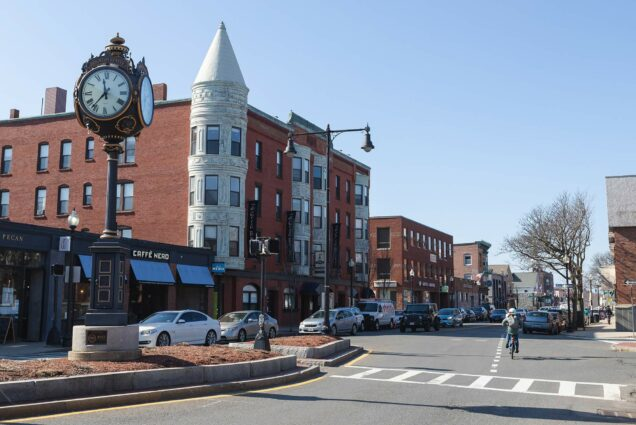 Photo of Washington Street in Brighton Center with old fashioned clock on the left; a biker rides down the street on the right.