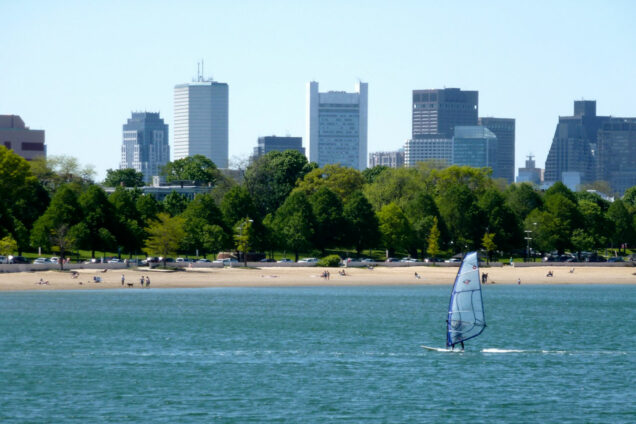 View of Pleasure Bay beach with the Boston skyline in the background and windsurfer on the water in the foreground.