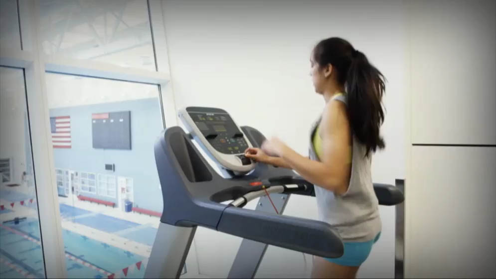woman running on a treadmill and adjusting the speed