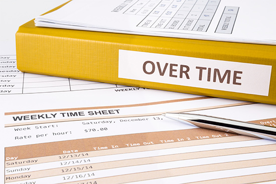 stock image showing time sheets and pay records calculating overtime pay