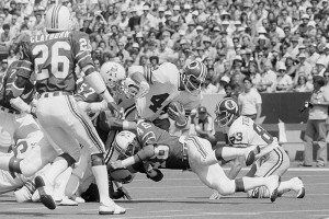 Washington Redskins' John Riggins busts through New England Patriots defensive player Tim Fox early in the first quarter at Foxboro, Mass., Sept. 3, 1978