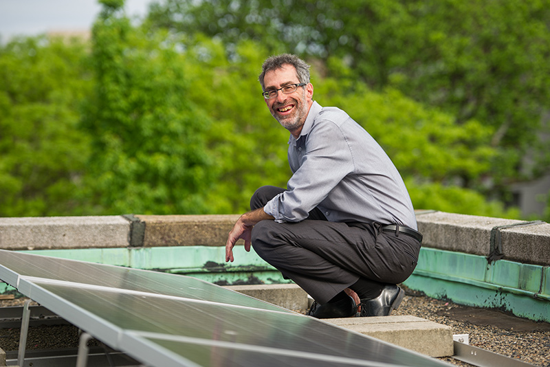 Robert Kaufman, professor of of earth and environment in Boston University's College of Arts and Sciences, with rooftop solar panels at Boston University