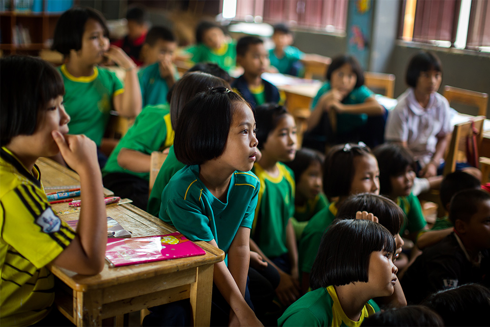 Thai schoolchildren listen to a class taught by BU Sargent College students and faculty during a public health education trip to Ban Doi Chaang village in Thailand