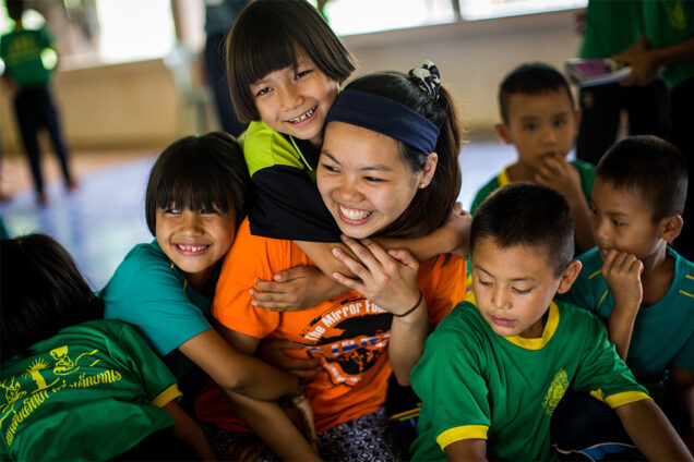 BU Sargent College student Grace Lei is hugged by children during a public health education trip to Ban Doi Chaang village in Thailand