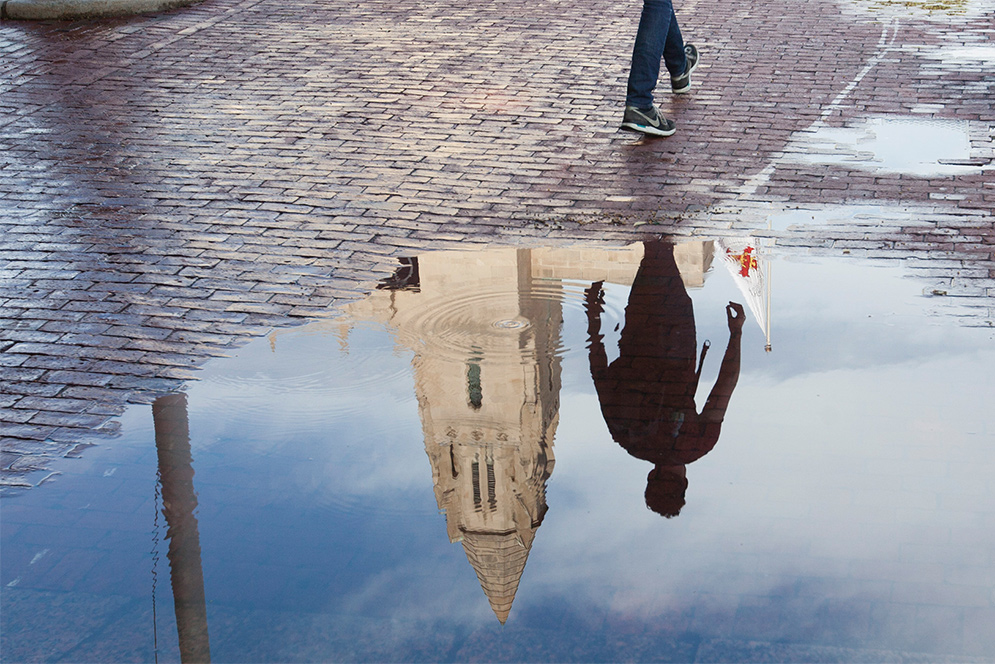a puddle reflects the a pedestrian passerby and building on the Boston University Charles River campus
