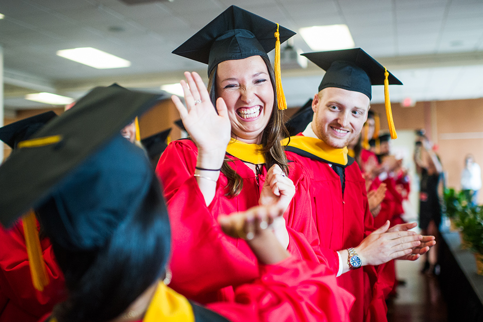 Jackie Price gives a high five to fellow graduate Sejal Thaker as Cole Turno looks on during the Physician Assistants Commencement ceremony.