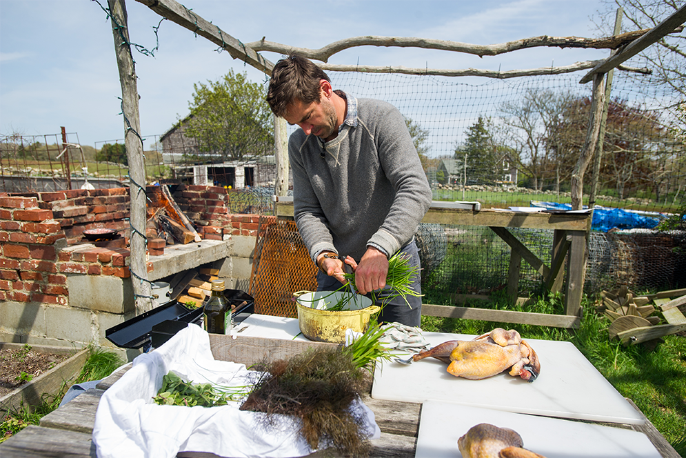Chef Chris Fischer prepares greens for dinner at Beetlebung Farm in Chilmark, Massachusetts on Marth's Vineyard