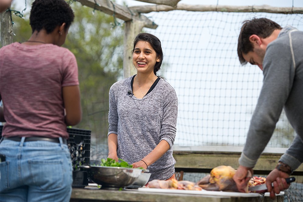 Boston University Gastronomy students Valencia Baker and Sonia Dovedy help Chef Chris Fischer prepare dinner at Beetlebung Farm in Chilmark, Massachusetts