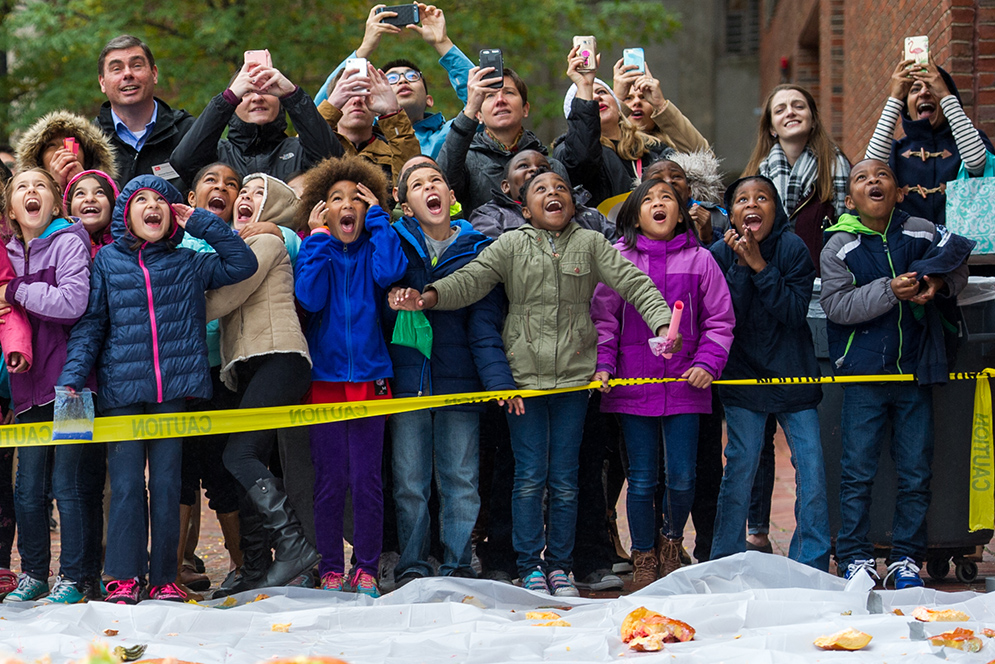 Children and spectators watch as pumpkins are dropped from the rooftop