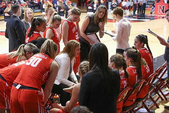 coach Katy Steding in huddle with the women's basketball team