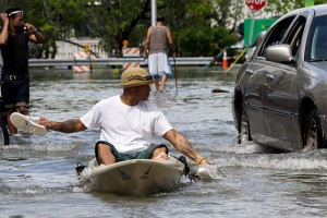 Juan Carlos Sanchez uses his shoes to paddle a kayak on a flooded street near Collins Ave.