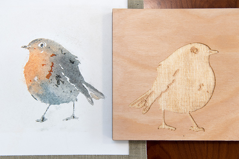 A detailed watercolor of a bird next to the laser-etched wood panel used to print the watercolor.