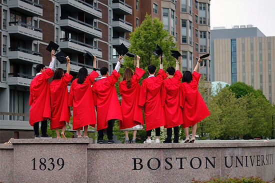 Graduating students of the Class of 2018 stand on top of the Boston University sign and wave goodbye to the University