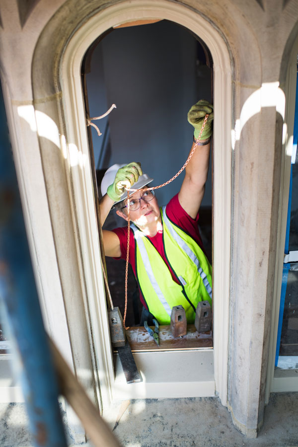 Alison Hardy (Questrom ) installs windows at BU Castle on Monday, July 2, 2918. She is the owner of Window Woman of New England, which has been hired as a subcontractor to restore the windows of the Castle. Photo by Jackie Ricciardi