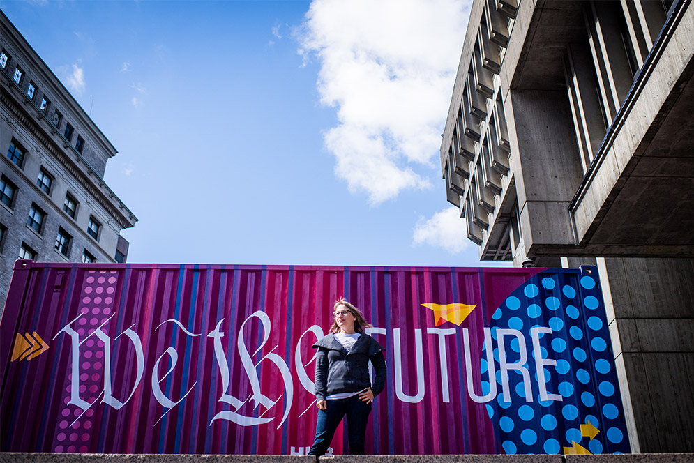 Director of Art and Creative Initiatives, HUBWeek, poses for a photo in front of a recycled shipping container transformed into a piece of artwork with the slogan 'We the Future'