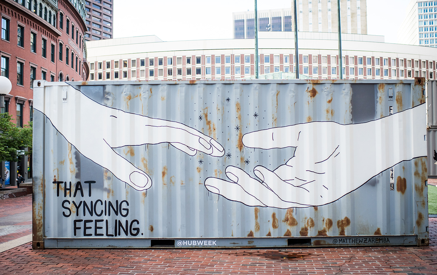 "An abandoned shipping container painted with a mural showing 2 hands reaching for each other and the phrase 'That Syncing Feeling."" The art will be featured at Boston's HUBWeek."