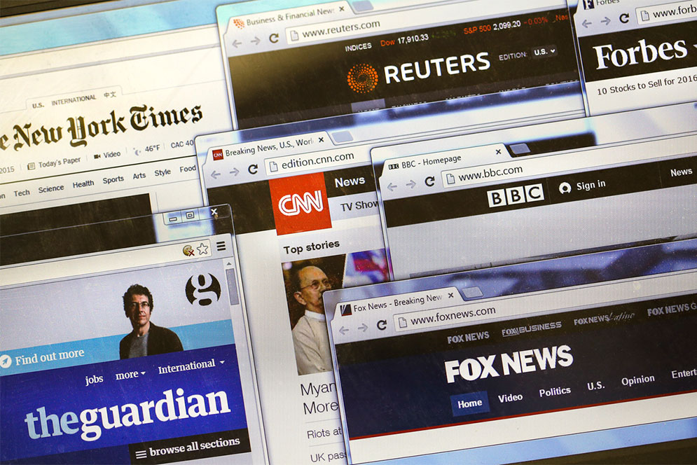 Composite image showing several open browswer windows displaying news websites such as New York Times, CNN, and The Guardian