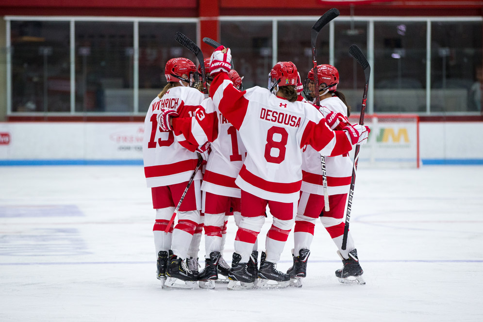 BU women's hockey team huddles on the ice