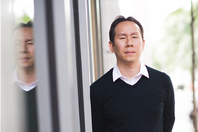 Portrait of Jerry Chen, Boston University College of Arts and Sciences assistant professor of biology, leaning against windows outside a building so that his reflection can be seen to the left.