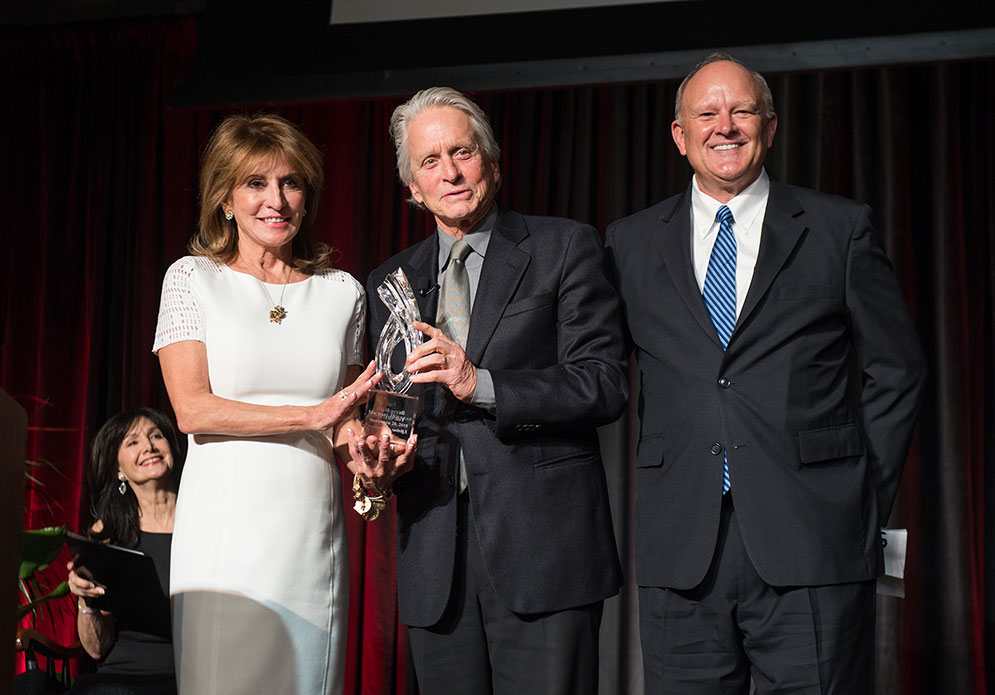 Actor Michael Douglas poses holding the Bette Davis Lifetime Achievement Award with Bette Davis Foundation founders Kathryn Sermak and Michael Merrill.