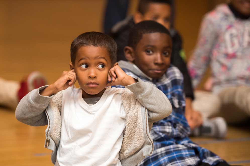 A kid covers his ears during the After-School Music program