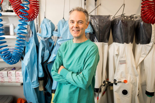 Robert Davey, infectious diseases researcher at the Boston University National Emerging Infectious Diseases Laboratories (NEIDL), poses for a portrait in front of hazmat suits like the ones he wears while conducting Biosafety Level 4 research in the NEIDL laboratory.