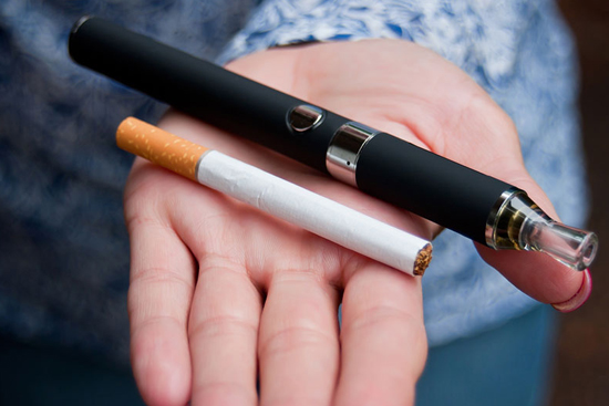 A woman's hand holding an e-cigarette vape pen and a traditional tobacco cigarette.