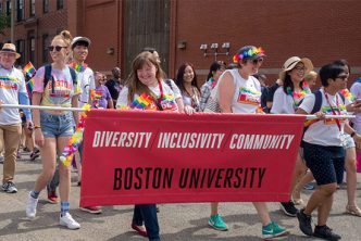 Boston University faculty and staff members march in the Boston Pride parade wearing t-shirts with the slogan 'Boston University Pride' and holding a banner with the slogan 'Diversity Inclusivity Community, Boston University'.