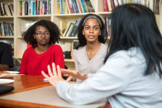 Shadae Leslie (COM'20) at left, and Nneka Oyigbo (CAS'20) listen to faculty member Sucharita Gupal